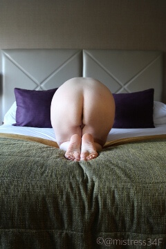 woman kneeling naked on the bed with the line of the headboard in line with her butt crack