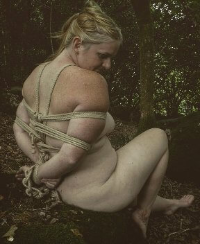 Nude woman in woodlands tied up with rope