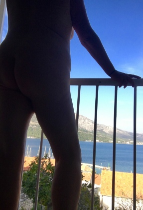 Woman naked on balcony with sea view in the distance