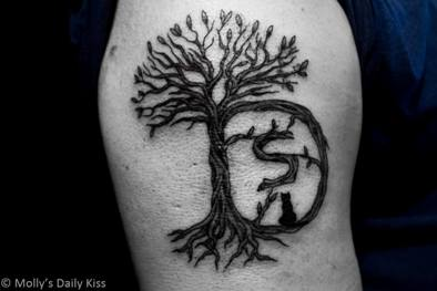 Tattoo of tree with letter D and small s in the trunk