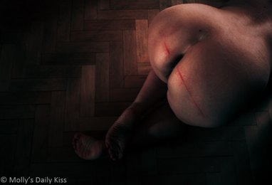 Woman kneeling with red strip welt on her bottom