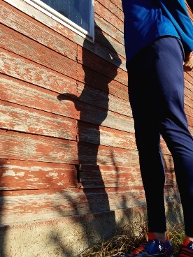Man is track pants next to his shadow on the wall that shows a silhouette shadow of him naked with an erect penis