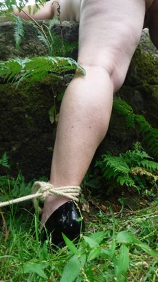Woman wearing black high heel tied with her leps open over rock outdoors