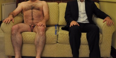 Man sitting on sofa naked next to himself in a suit