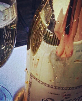 Reflection in champagne bottle of topless woman