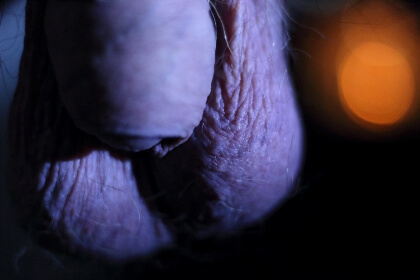 close up shot of head of mans penis and testicles with bright bokeh spot in the back ground