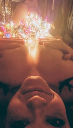 Woman laying covered in fairy lights looking up at the camera