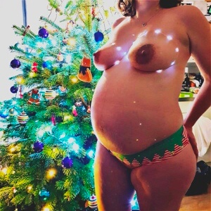 Nude of pregnant woman in christmas panties by christmas tree