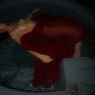 Woman floating in hot tub with red wrap that looks like blood in the water