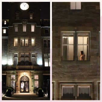 View of front of hotel with naked woman in one of the windows