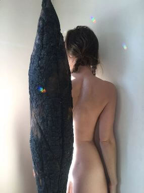 Naked woman next to large carchoal