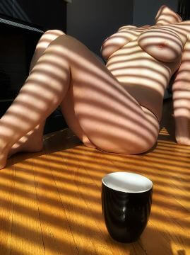 Nude woman laying in stripes of sunlight through a blind