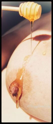 Honey being poured on woman's breast