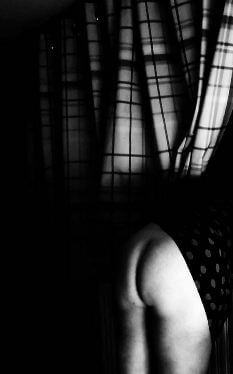 Black and white of woman's bare bottom sticking out of curtains