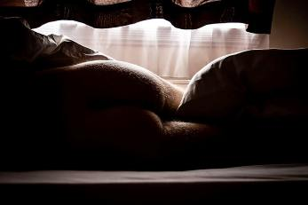 Man's bottom laying on the bed in early monring light