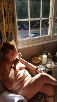 Woman sitting by the window eating breakfast naked