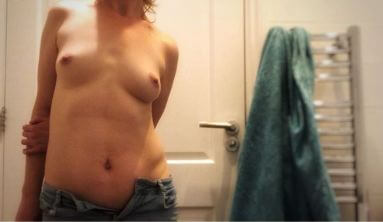 Woman topless in bathroom mirror with her jeans unbuttoned