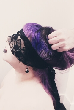 Woman with purple hair and blidfold having her head pulled back