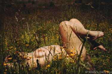 Nude woman laying in the buttercups