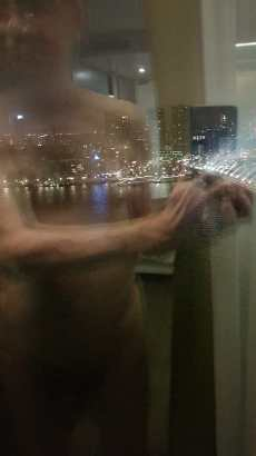 Naked man standing at the window with city lights reflected upon the glass