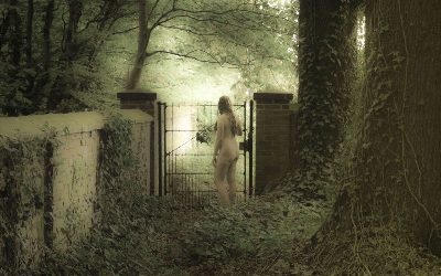 Nude woman standing by garden gate in magical woodland