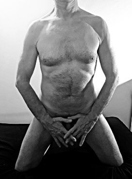 black and white nude of man covering his penis with his hands