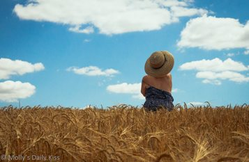 woman in large sunhat in wheat field with her dress slipping down