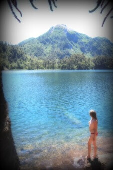 Topless woman standing by beautiful blue water
