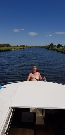Woman topless stiring boat with mastectomy