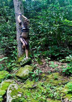 Woman tied to tree in forest wearing black lingerie