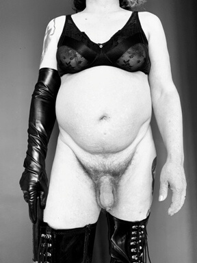 Man in bra and thigh high boots holding flogger
