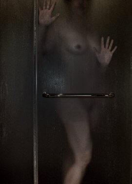 Woman nude behind glass shower door