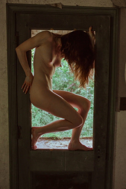 Nude woman in doorway window