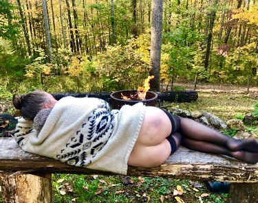 Woman laying on bench in the woods wearing sweater and stockings