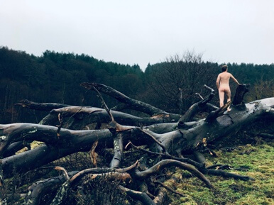 Man standing naked in fallen tree