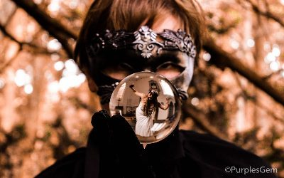 man wearing mask looking into crystal ball with girl stuck inside the ball