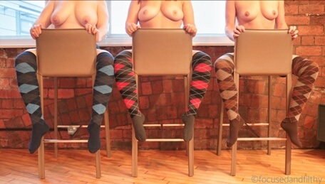 Three women sitting on stools topless wearing striped long socks