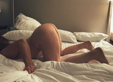 nude woman face down in the bed with her bum in the air