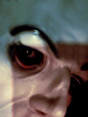 weird creepy red eyes through a mask