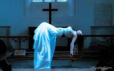 woman in wedding dress hainging in the air in front of church alter