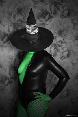 woman with green skin wearing witches hat