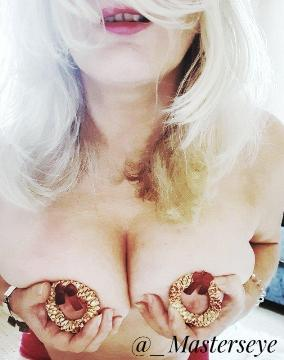 Woman holding baubales over her breasts