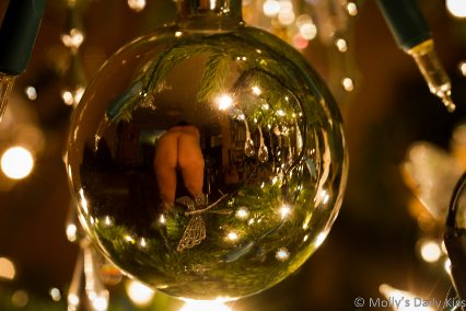 Reflection of naked woman beinding over in a christmas bauble