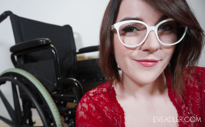 Woman with cheeky grin looking at the camera sitting in front of wheel chair