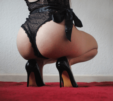 Woman wearing black thing and bow in black high heels crouching down