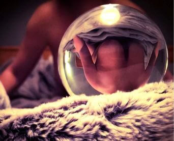 upside down reflection of topless woman in glass ball