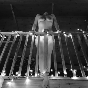 looking up at nude woman leaning over landing bannisters