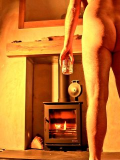 Nude mand holding drinking in front of wood buring stove
