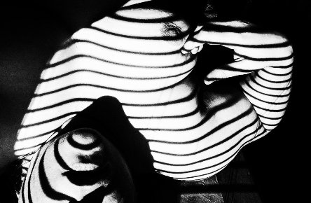 balck and white image of woman in the shadows on blinds