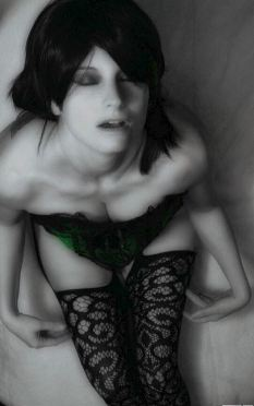 woman wearing green corset looking up at the camera